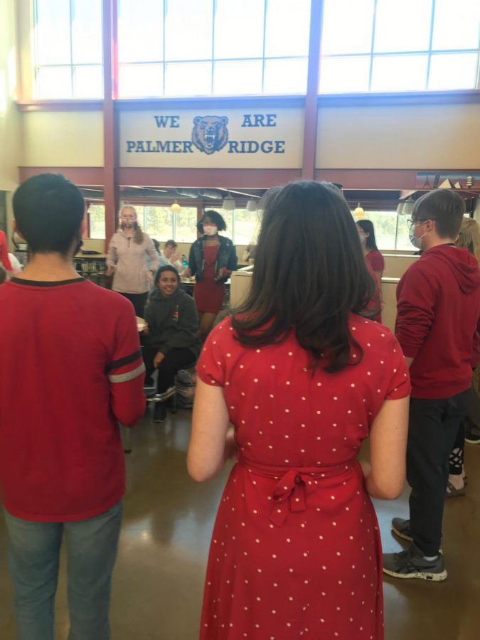 The talented choir gifts a valentune to a student in the cafeteria.